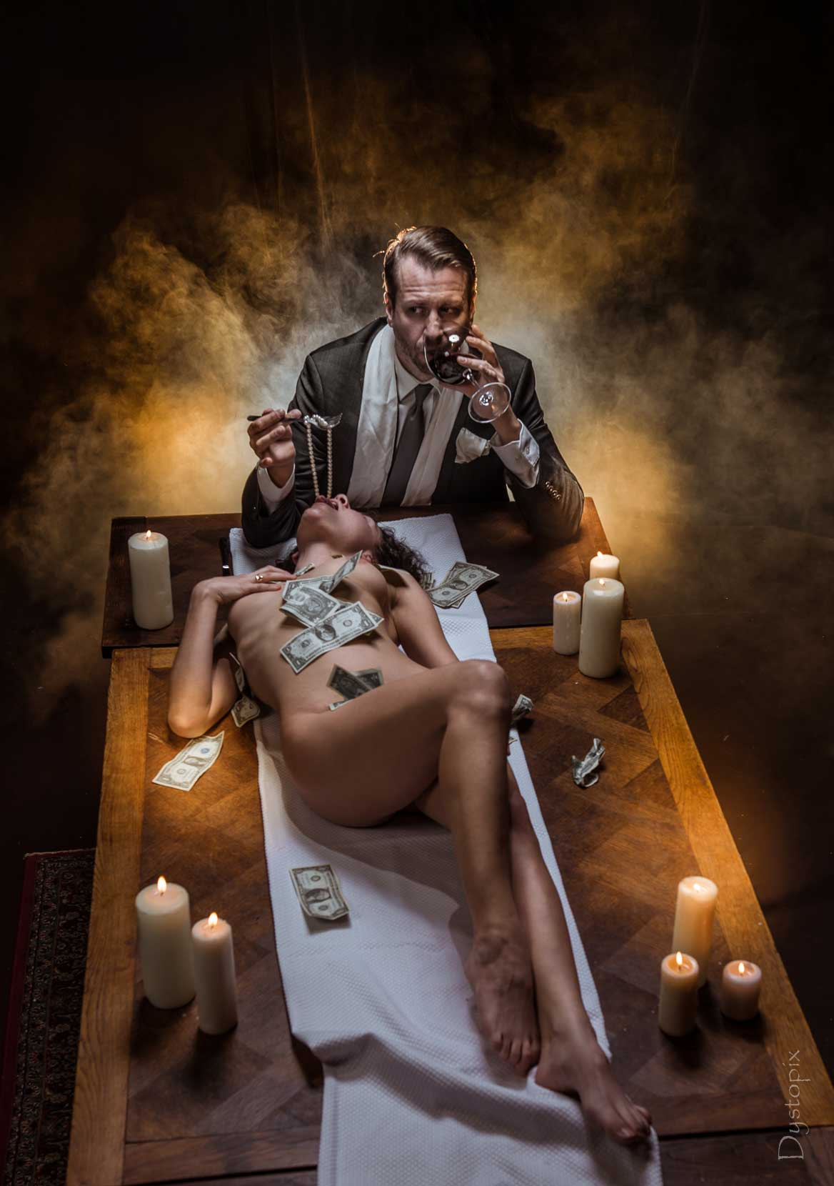 Man eating dinner with a woman nude on the table