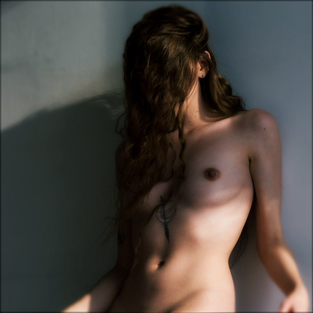 Woman posing nude against wall